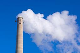 Smokestack and Gas Emissions Against Blue Sky